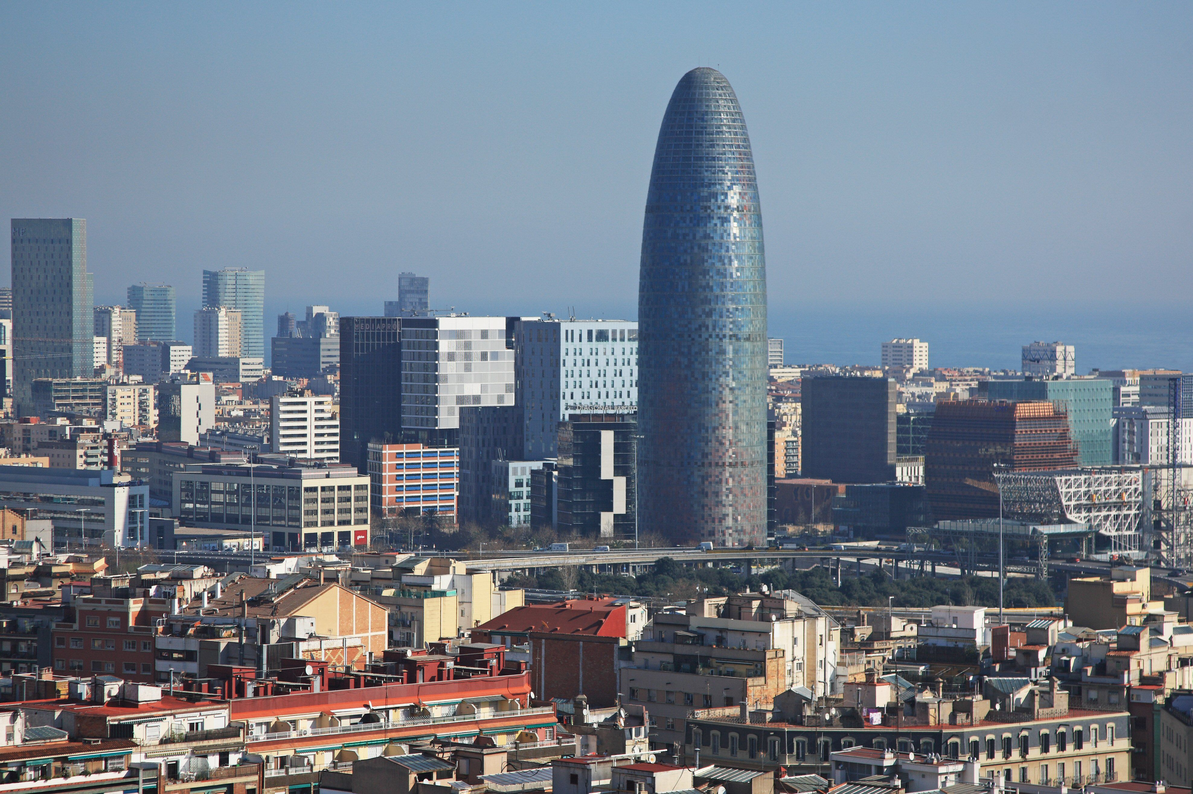 city scene with large missile-like skyscraper rising amongst rectangular buildings