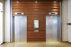 A pair of elevator doors set in the wooden wall of a lobby