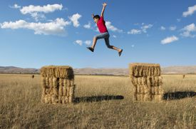 A boy jumping from one to another hay stack.