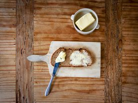 Cutting board with buttered bread and a container of butter.