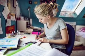 Young woman doing her homework at her desk