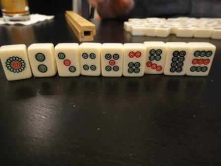 The stones suit of a standard set of Mahjong tiles standing up on a table.