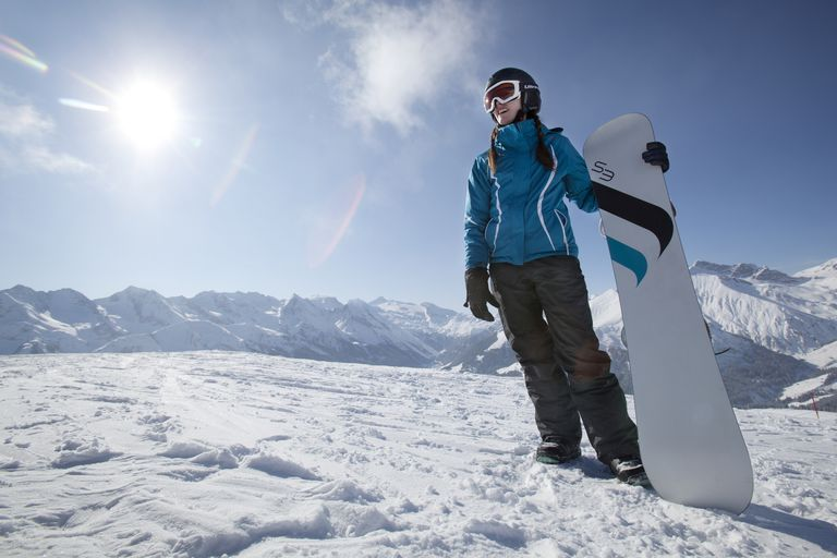 Young woman standing on mountain with her snowboard