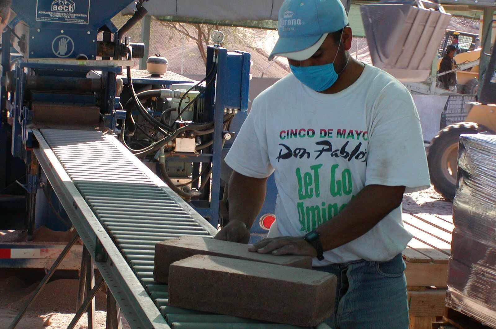 man in t-shirt, cap, and surgical mask examines earth block on a conveyor roller