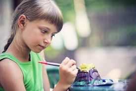 Girl painting clay volcano outside.