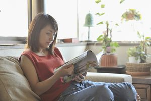 Woman reading a magazine while sitting on a couch