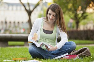 A student sitting in the grass studying