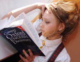 Young girl looking at an English dictionary.