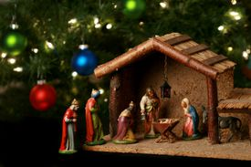 A nativity scene in front of a Christmas tree.
