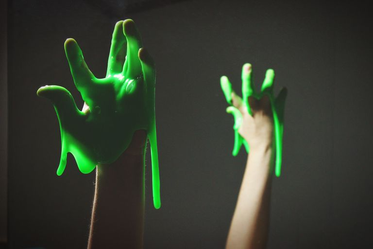 Cropped Hand With Green Slime Against Black Background