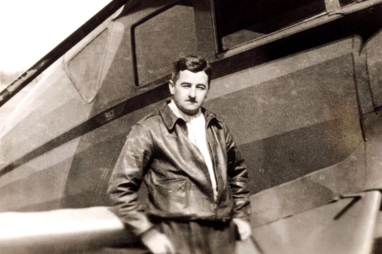 William Faulkner stands before a small propeller plane