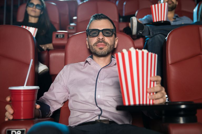 Man with drink and popcorn in a movie theater