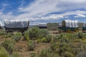 Covered wagons in a circle on the prairie under a blue sky.