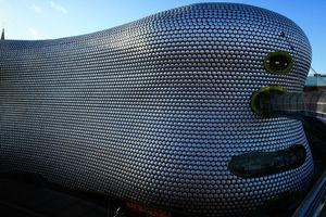 free-flowing multi-story building covered with silver discs, openings on the narrow end