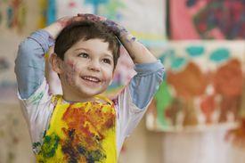 Messy Caucasian boy in art class
