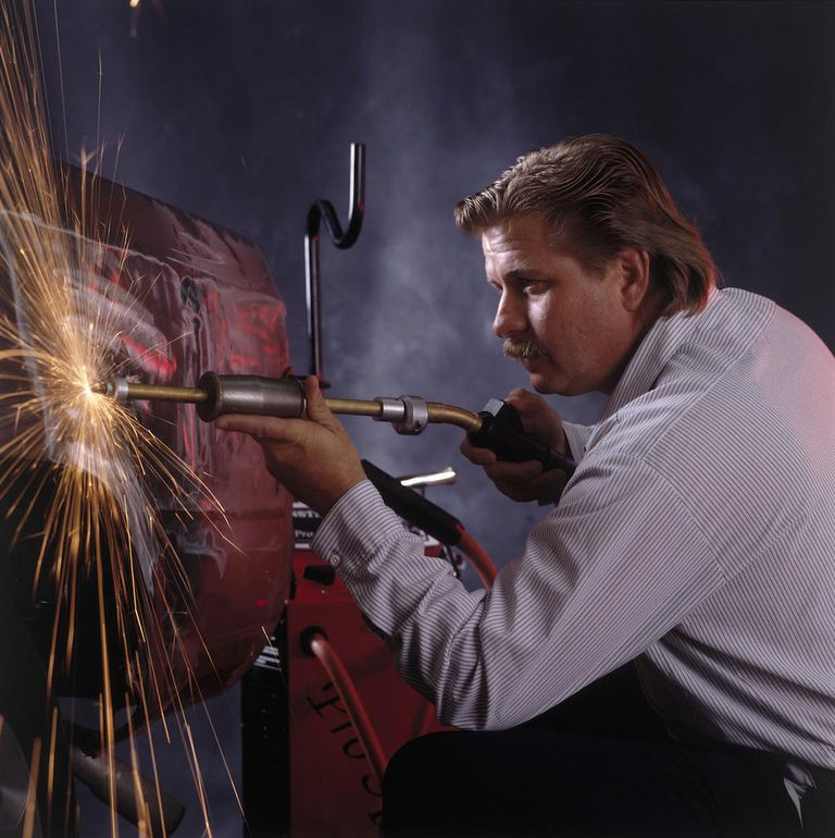 Man repairing body of car using welding equipment