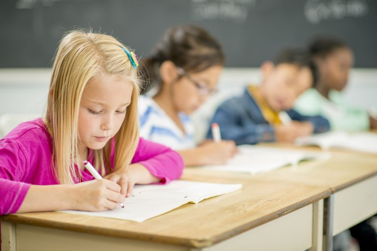 third graders writing at desks in class