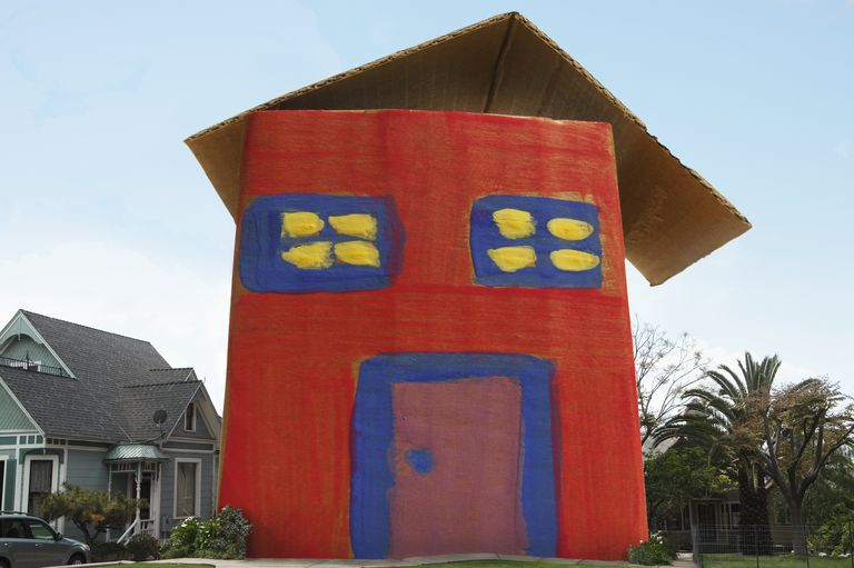 Full Sized Red Blue And Yellow Cardboard House In A Neighborhood