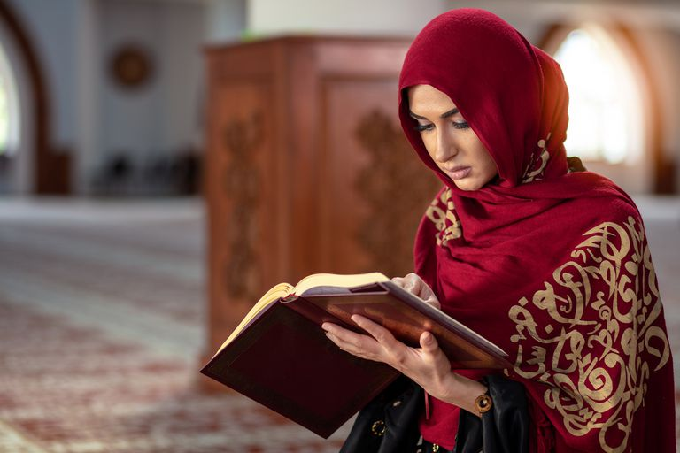 Young Muslim woman praying in mosque with Quran
