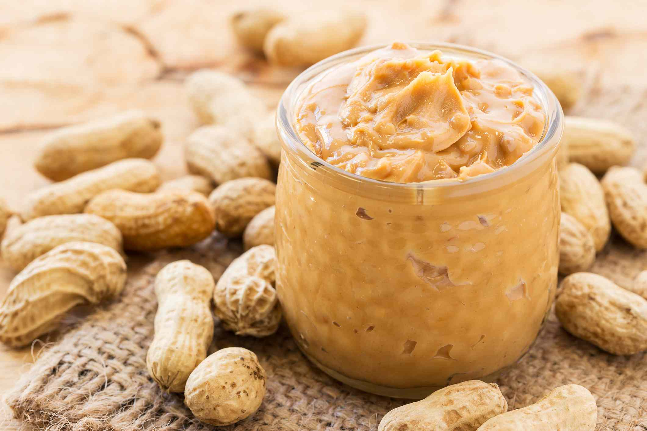 peanut butter jar in front of whole peanuts