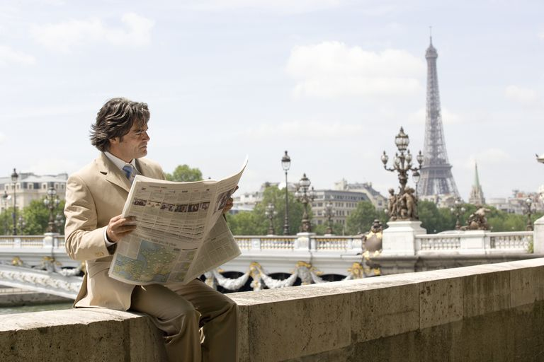 Man reading a French newspaper in Paris with the Eiffel Tower in the background.