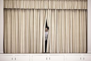 A man peering out from behind a stage curtain symbolizes Goffman's front stage and back stage dichotomy of behavior.