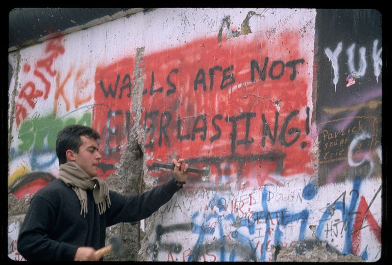 Man chiseling on Berlin Wall