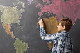 Child drawing world map on a blackboard