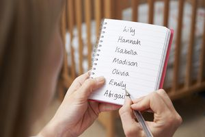 Woman Writing Possible Names For Baby Girl In Nursery