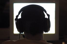 Silhouette of back of a person's head with large headphones in computer glow