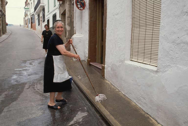 Woman Cleaning Sidewalk in Spain