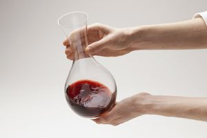 person shaking wine in a decanter