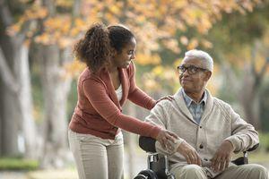 Social worker helping man in wheelchair
