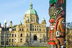 Parliament Building in Victoria, B.C., across the street from a handmade aboriginal totem pole with bears