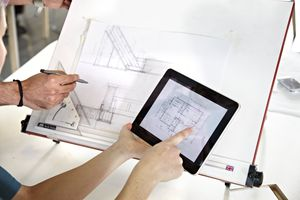 Hands pointing to a floor plan on a digital tablet, with architectural drawings being modified behind it.