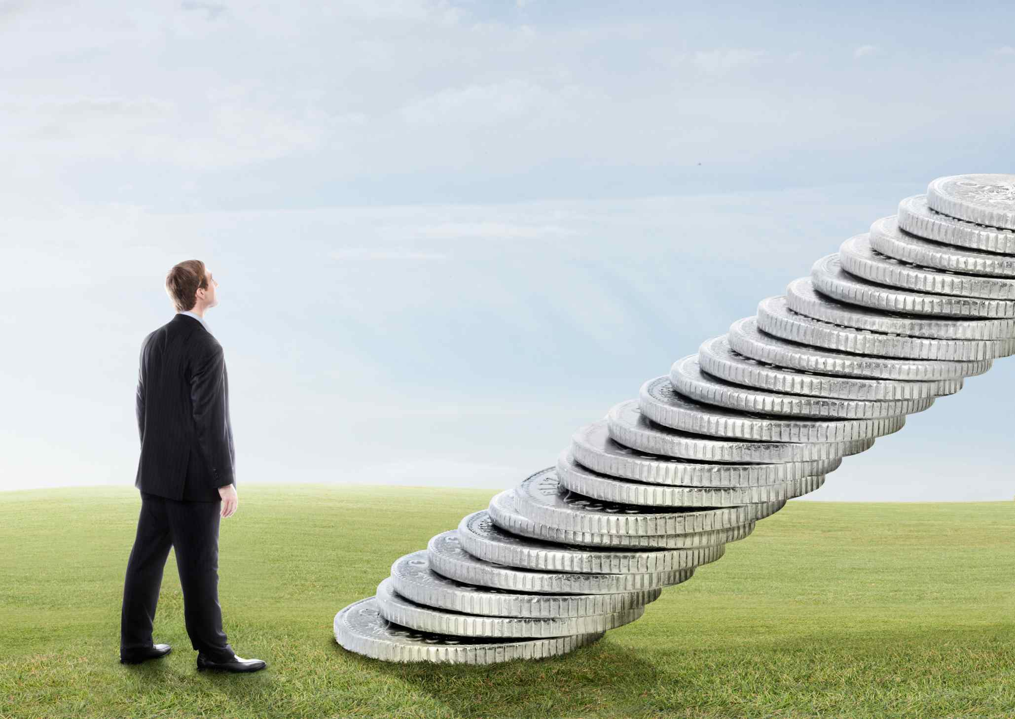 Persona frente a una escalera de dinero.