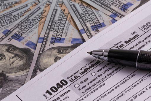 US Tax Return Form 1040 and 100 USD Bills