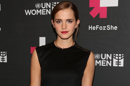 Emma Watson posing in front of UN Women's 'HeForShe' sign.