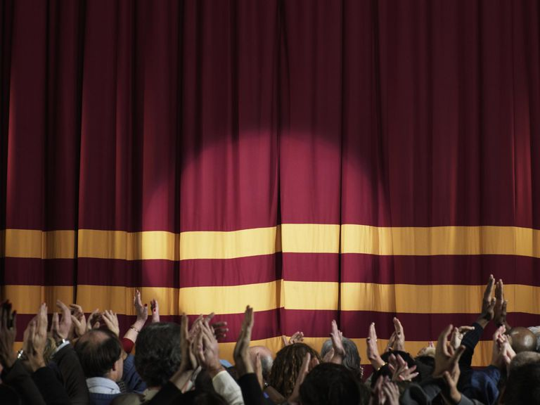 Spotlight on stage curtains, audience applauding in foreground