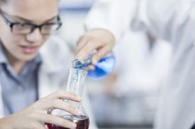Tow people in lab coats combine colored liquids from different flasks