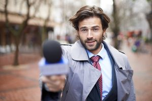 reporter pointing microphone at the camera