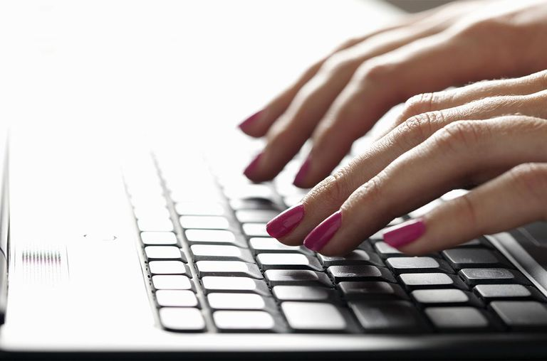 Close up of hands on laptop keyboard