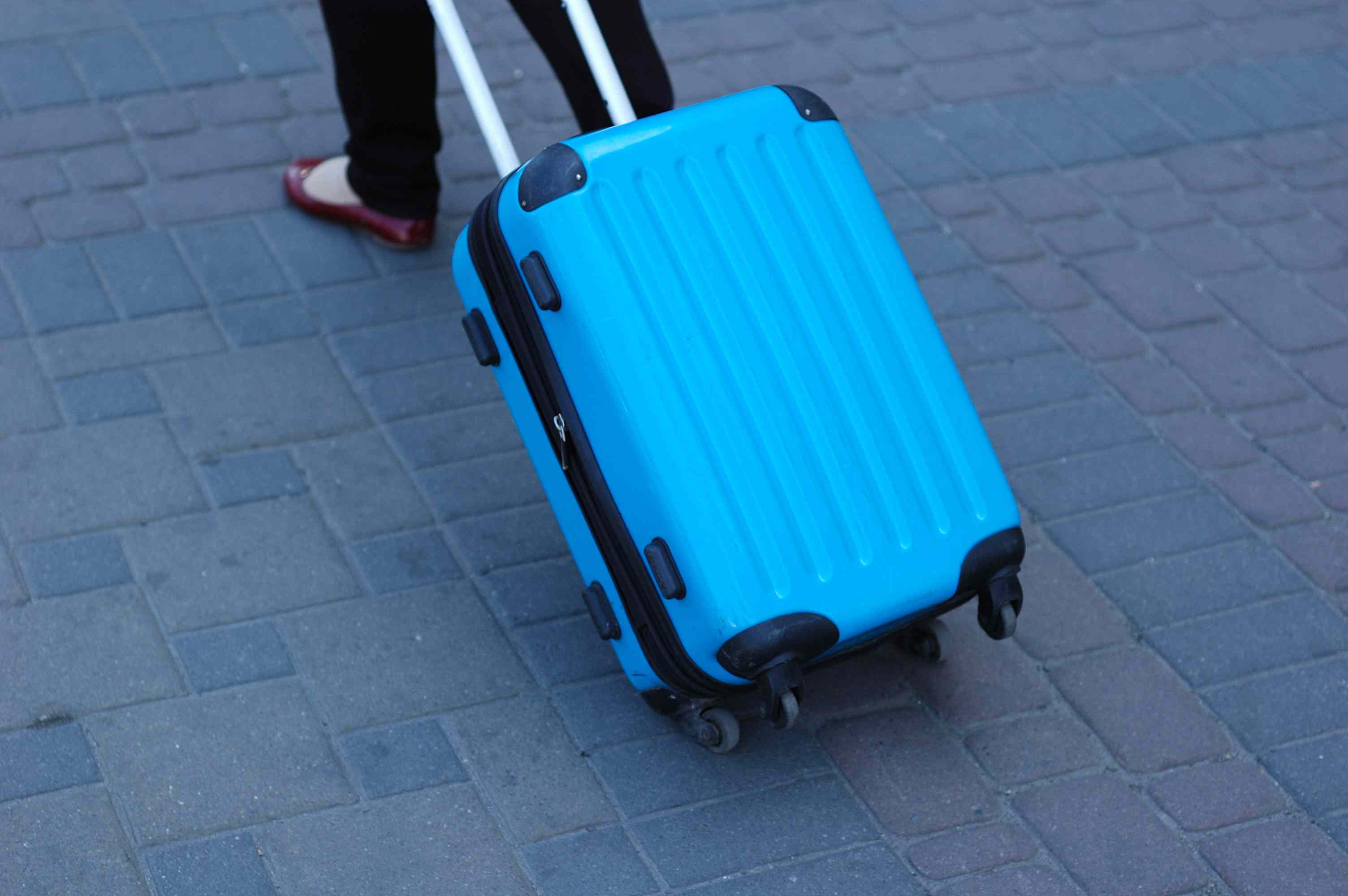 A blue rolling backpack is taken along the path.