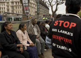 Man wearing anti-genocide shirt among protesters in London.
