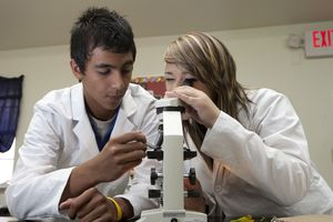 High school students using a microscope