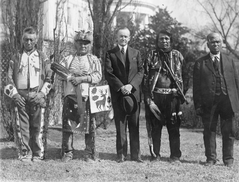 Black and white 1924 photo of U.S. President Calvin Coolidge with four Osage Indians in front of the White House
