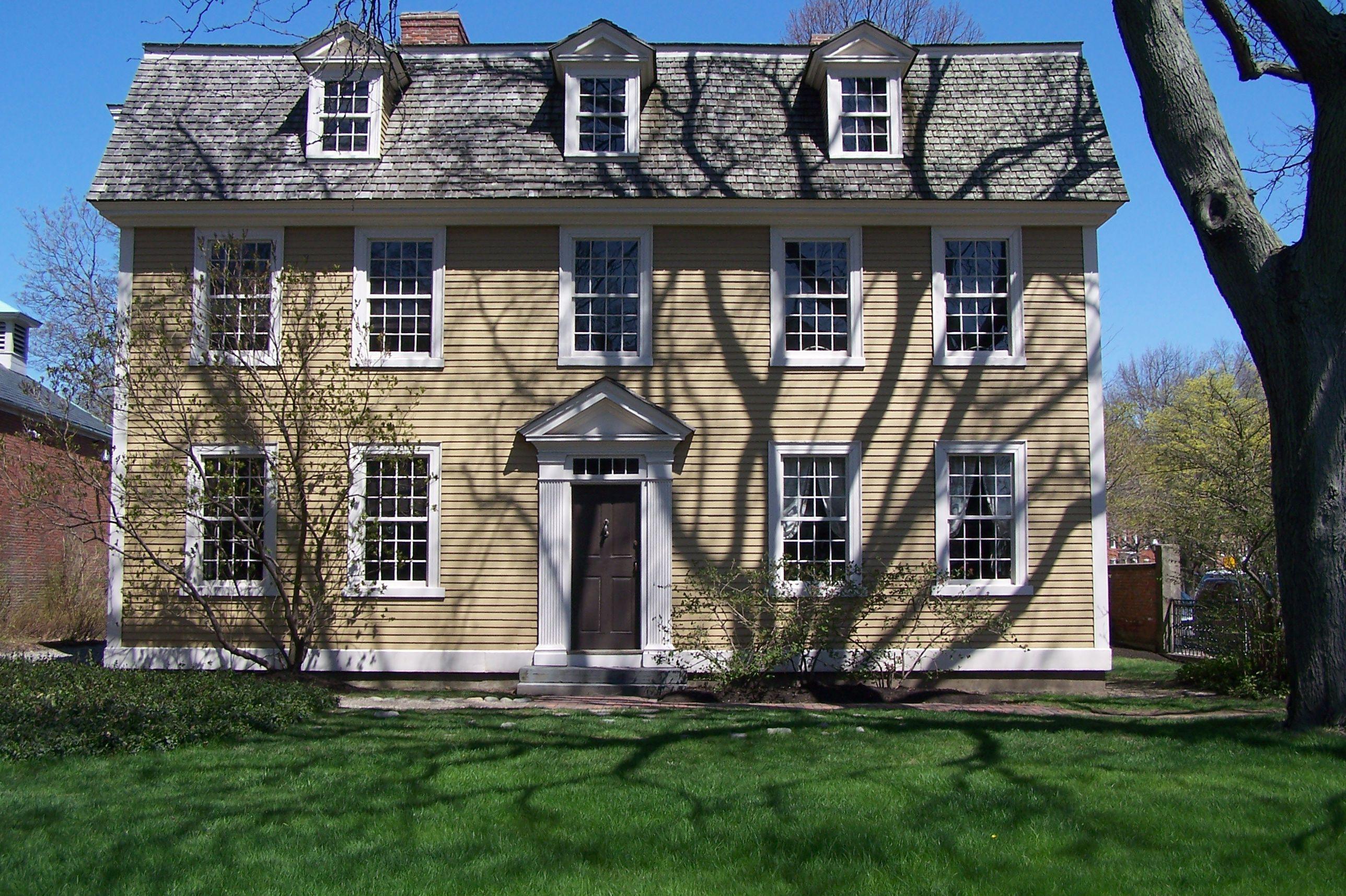 façade d'une maison de deux étages avec trois lucarnes dans un toit en croupe, Fronton sur la porte d'entrée, deux 12 sur 12 fenêtres de chaque côté de la porte et cinq dans la partie supérieure du deuxième étage - revêtement de couleur jaune-or garniture blanche