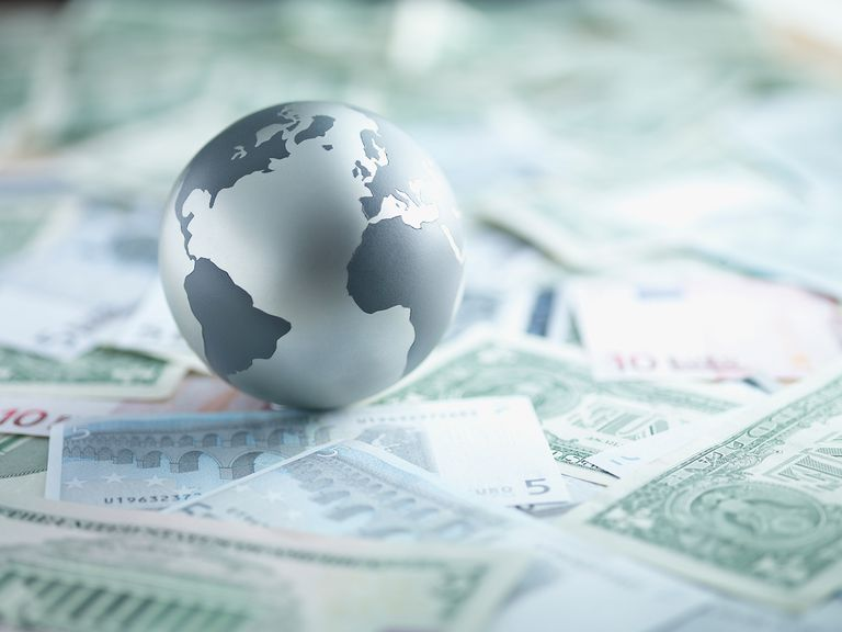 Metal globe resting on paper currency.