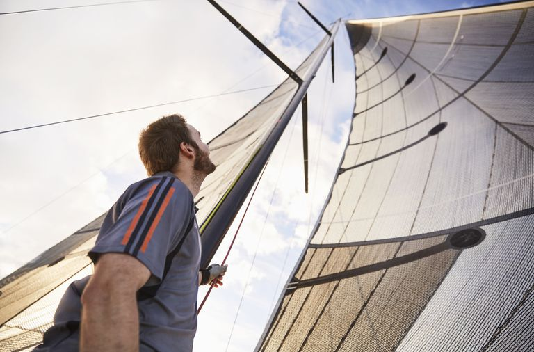 Man looking up at sailboat sails