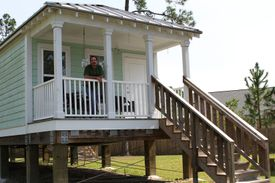man stands on front porch of elevated shotgun-style house